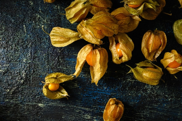 Physalis berries are scattered on a dark aged background, top view