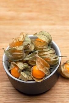 木製のテーブルの上のサイサリスの果実。木の背景の上のカップに甘い黄色のサイサリスベリー。