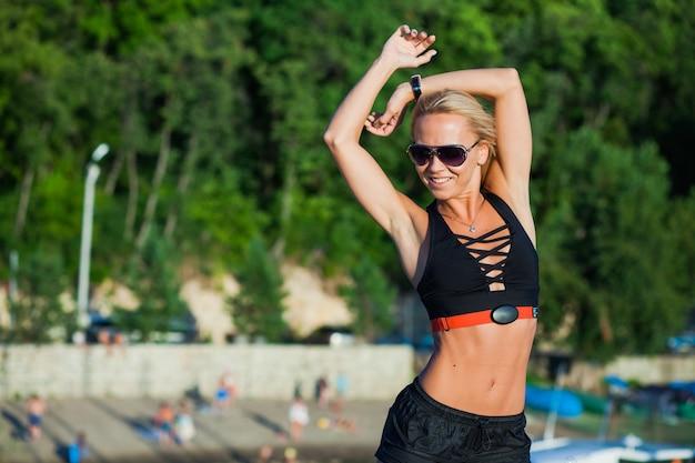 フィット女性の身体活動ベルトフィットネストラッカー。屋外で美しい女性アスリートのトレーニング。