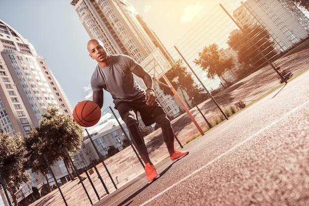 身体活動。バスケットボールをしながらあなたに微笑んで喜んで幸せな男