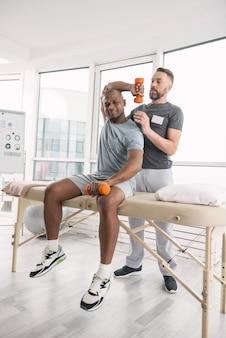 身体活動。トレーニングをしながら医療用ソファに座って喜んで素敵な若い男