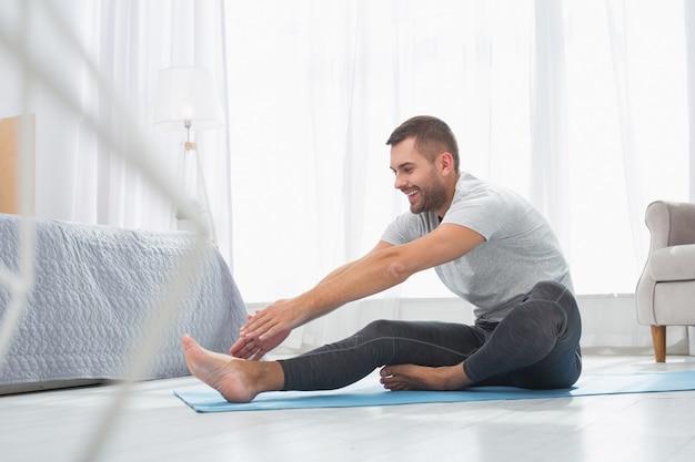 身体活動。彼の足に触れようとしている間、前に曲がっている素敵なポジティブな男
