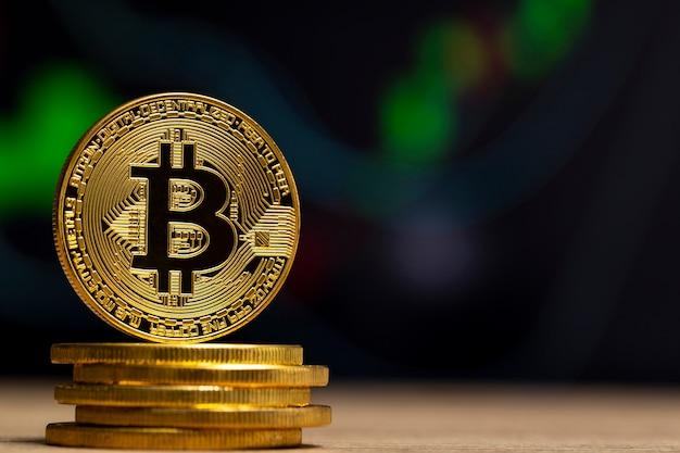 青いグラフの前の木製のテーブルに立っている物理的なビットコイン