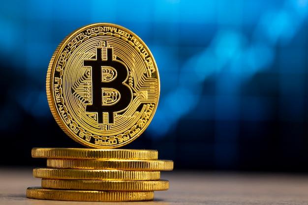 青いグラフの前にある木製のテーブルに立っている物理的なビットコイン