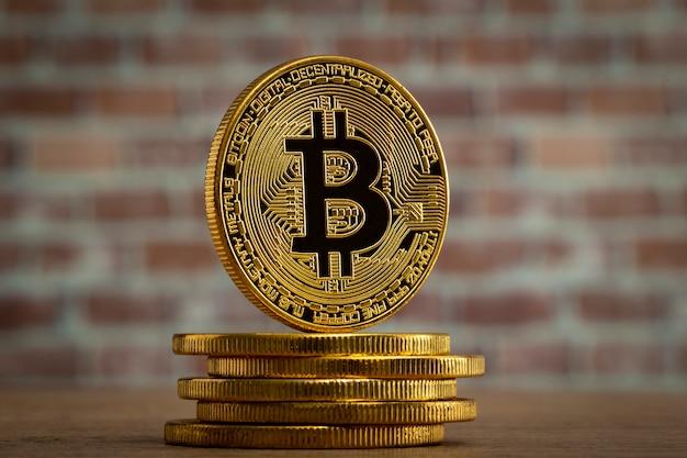 レンガの壁の前の木製のテーブルに立っている物理的なビットコイン