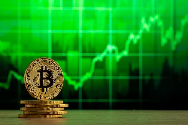 Физический биткойн, стоящий за деревянным столом перед зеленым графиком. концепция рынка bitcoin bull.