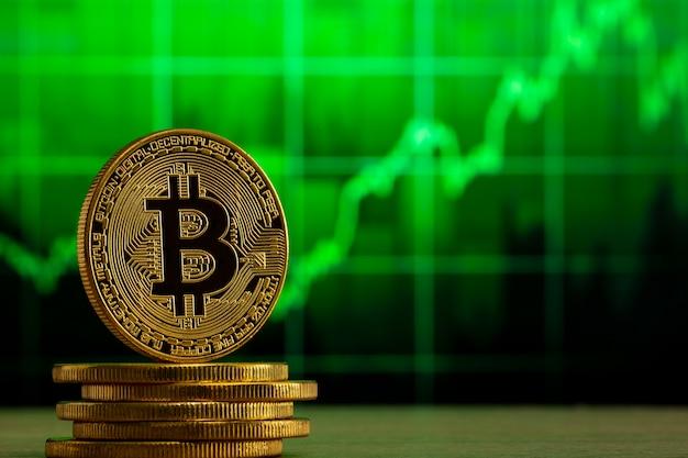 緑のグラフの前の木製のテーブルに立っている物理的なビットコイン。ビットコインブルマーケットのコンセプト。