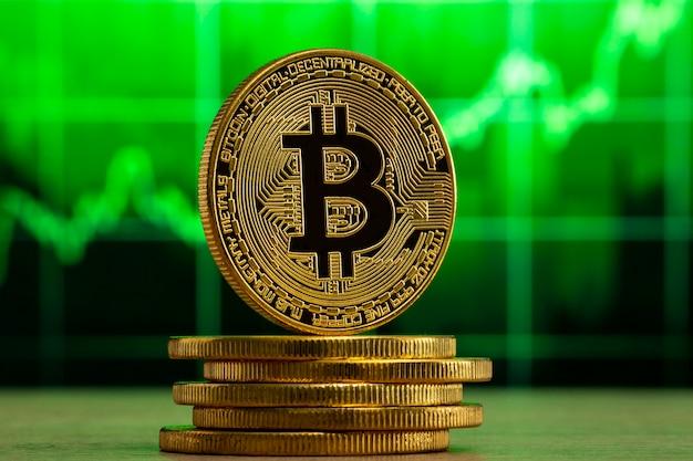 緑のグラフの前にある木製のテーブルに立っている物理的なビットコイン。ビットコイン強気相場の概念。