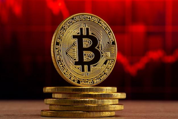 赤いグラフの前の木製のテーブルに立っている物理的なビットコイン。ビットコインベアマーケットのコンセプト