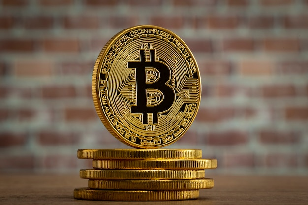 Physical bitcoin standing at a wood table in front of a brick wal