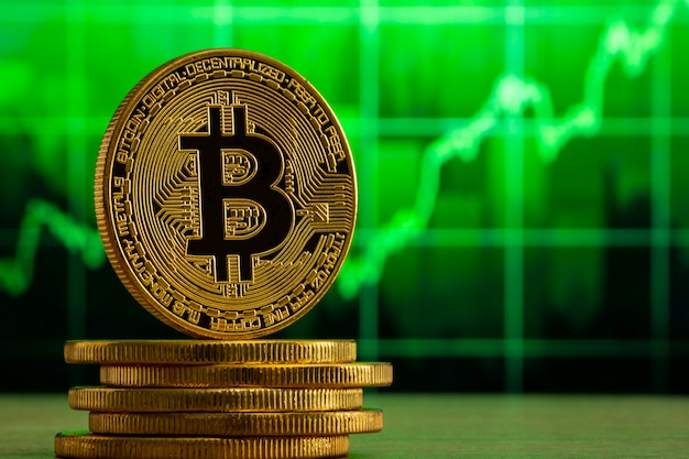 Physical bitcoin standing on a wood table in front of a green graph