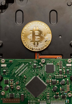 Physical bitcoin on top of a circuit board, modern digital money concept.