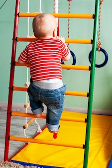 Physical development of child. childrens sport gym complex at home. exercise on simulator. healthy lifestyle