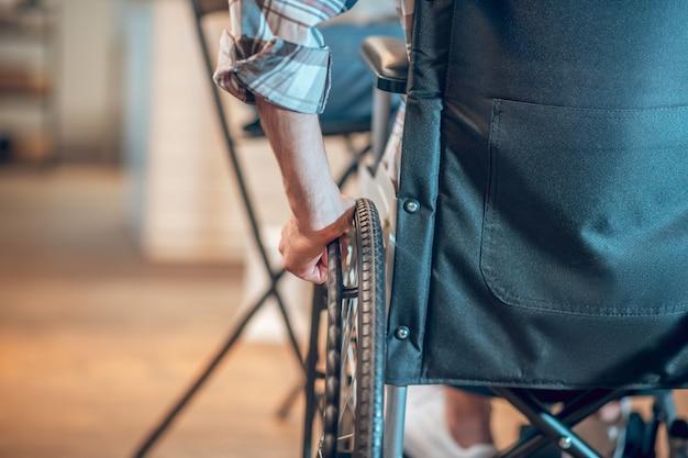 신체 장애. 실내에서 휠체어에 앉아 바퀴를 만지는 격자 무늬 셔츠를 입은 남자의 손, 얼굴은 보이지 않습니다