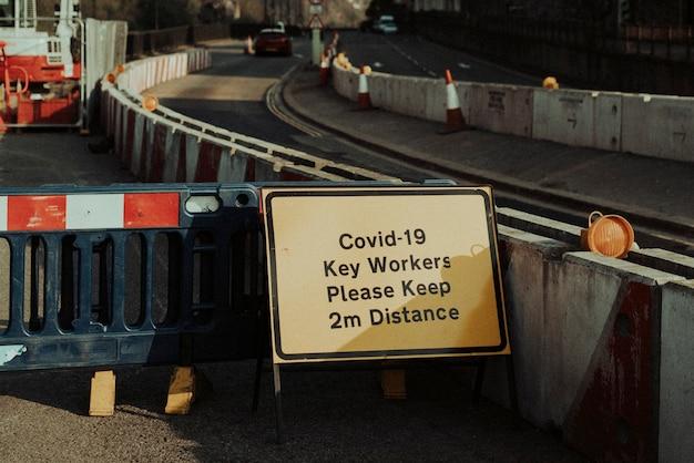 Covid-19 전염병 동안 길가 건설 노동자를 위한 물리적 거리 경고 표지판