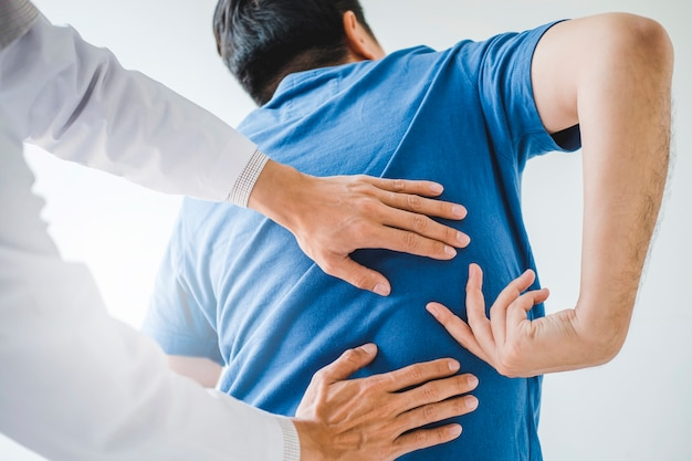 Physical doctor consulting with patient about back problems physical therapy