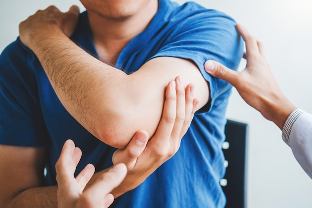 Physical doctor consulting with patient about elbow muscule pain problems