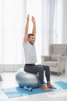 Physical exercise. positive happy man holding his hands up while doing an exercise on a med ball Premium Photo