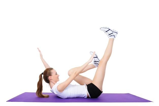 Esercizi fisici di giovane bella donna - isolata su bianco