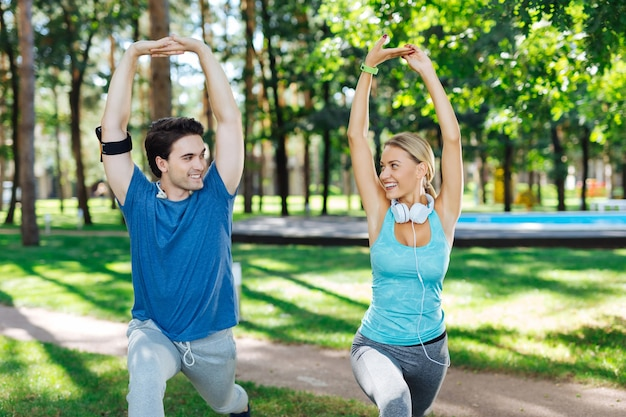 Physical exercising. joyful positive couple holding their hands up while doing physical exercising