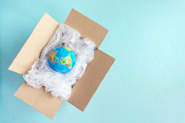 Physical globe, earth in plastic wrap in carton box on blue background