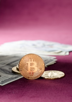 Physical gold bitcoin coin against dollar bills on a purple background.