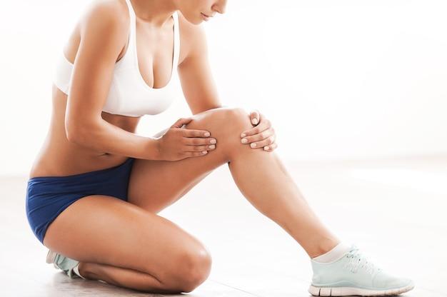신체 상해. 바닥에 무릎을 꿇고 부상당한 무릎을 만지는 스포츠 의류를 입은 아름다운 젊은 여성의 이미지