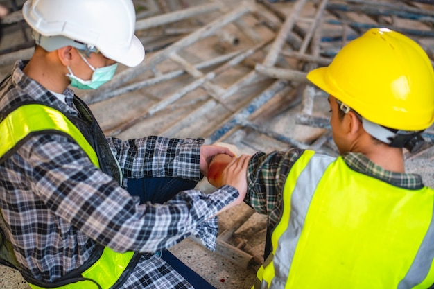 Physical injury at work of construction worker. injury bleeding from work accident in pile of scaffolding steel falling down to impinge the arm.