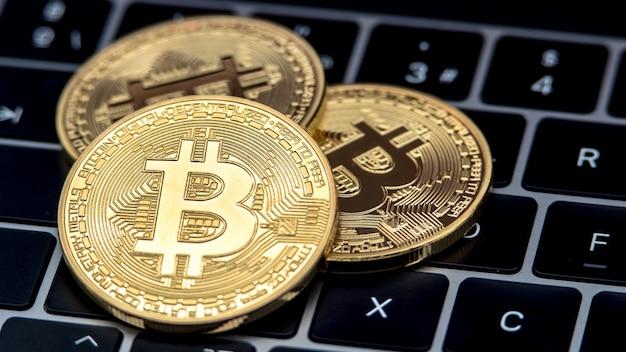 Физическая металлическая золотая валюта bitcoin на клавиатуре портативного компьютера. всемирные виртуальные интернет-деньги. цифровая монета в киберпространстве, криптовалюта, золото, btc. хорошие инвестиции в будущем онлайн-платеж
