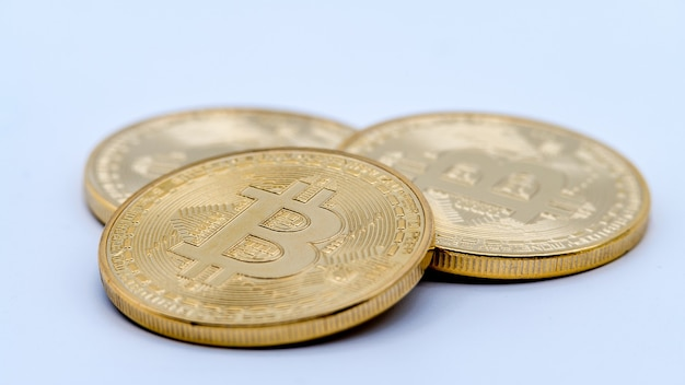Physical metal golden bitcoin currency on white wall. new worldwide virtual internet money. digital coin in cyberspace, cryptocurrency gold btc. good investment future of online payment