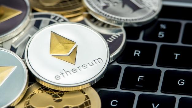 Физическая металлическая серебряная валюта ethereum, клавиатура ноутбука. всемирные виртуальные интернет-деньги. цифровая монета etherum, киберпространство, криптовалюта eth. хорошие инвестиции в будущем онлайн-платеж