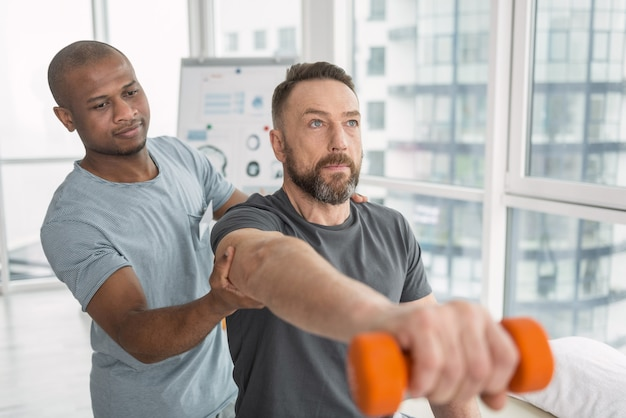 身体リハビリテーション。彼のセラピストに助けられながら身体運動をしている素敵な楽しい成人男性