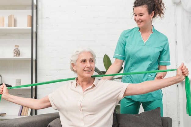 Physical therapist assisting old woman stretching with green exercise band