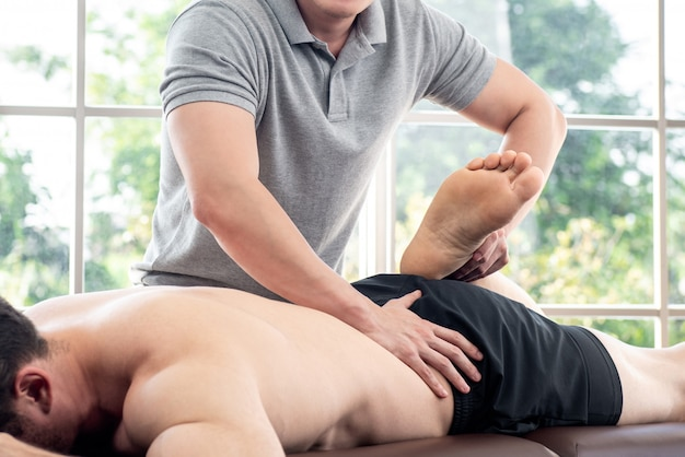 Physical therapist giving massage and stretching to athlete male patient