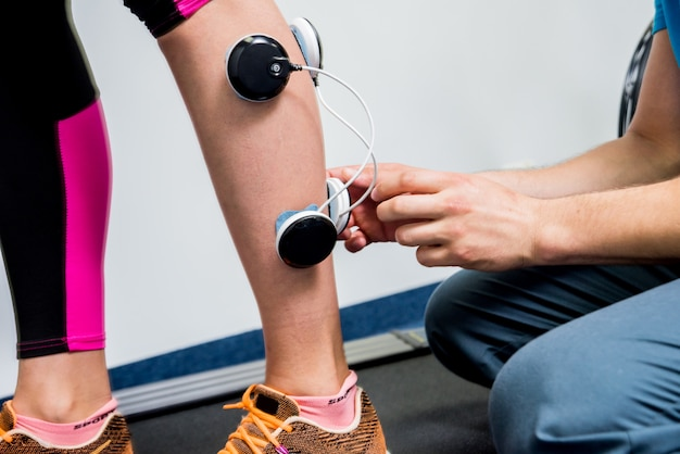 Physical therapist install electrostimulator on the muscles of the legs.