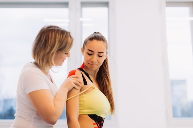 Physical therapist placing kinesio tape on woman patient's shoulder and neck