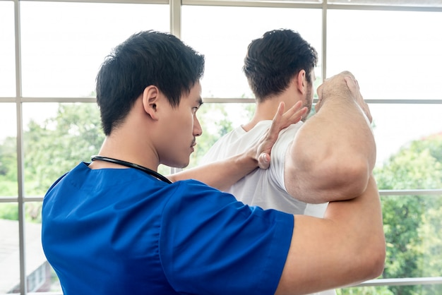 Physical therapist stretching athlete male patient shoulder and arm