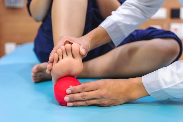 理学療法士は、足の裏の痛みを軽減するためにボールを使用する際に患者に助言を与えています。