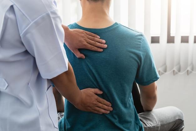 물리 치료사는 클리닉에서 남성 환자를 위해 일하고 있습니다.