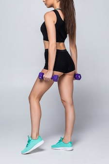 Тренировка физической подготовки молодой красивой женщины с изолированными гантелями