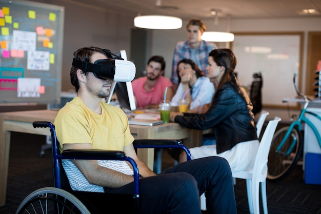 Человек с ограниченными физическими возможностями на инвалидной коляске с помощью гарнитуры vr в офисе