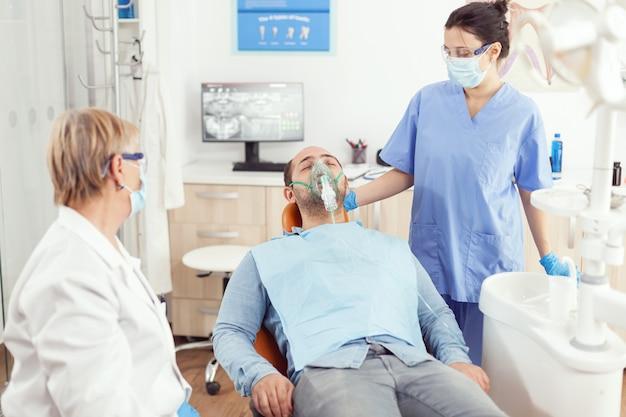 口腔病学キャビネットの歯科用椅子に立っている歯の手術の前に酸素マスクを置く医師の助手