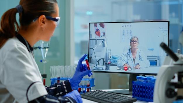 Врач-врач, предлагающий медицинские онлайн-советы студенту-химику с помощью пк. ученый держит образец крови во время онлайн-обсуждения, виртуальной конференции, помогает по телемедицине, поддержке здравоохранения