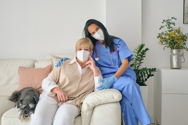 Physician embracing patient on sofa with dog after examination