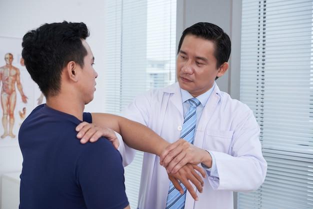 Physician examining sportsman at clinic