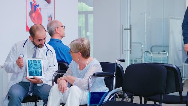 Врач держит планшетный пк во время обсуждения с пожилой женщиной-инвалидом в инвалидной коляске. мужчина прибывает в клинику для медицинского обследования. старик в зоне ожидания больницы.