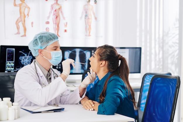 의료용 마스크와 고무 장갑을 착용 한 의사가 여성 환자에게 입을 열어 그녀의 목을 확인할 수 있도록 요청