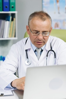 白衣を着た医師が、病院のオフィスの机の後ろで病歴を閲覧している