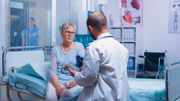 디지털 안압계로 혈압을 측정하는 의사는 병원 침대에 앉아 있는 동안 현대 개인 클리닉에서 노년의 은퇴한 여성에게 혈압을 측정합니다. 의료 의료 의료 시스템 질병 치료