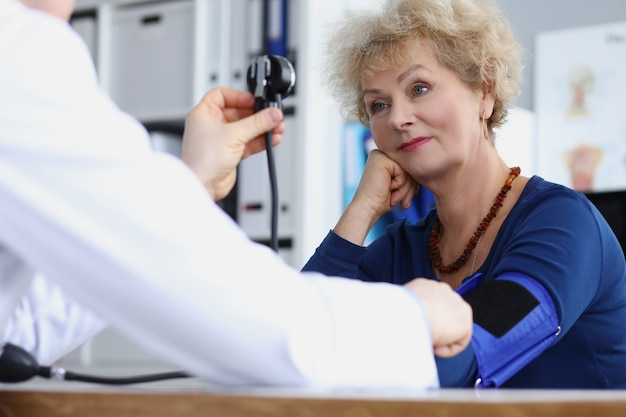 Physician therapist measures blood pressure of elderly woman